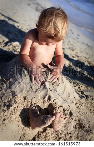 Little toddler overwhelmed in beach sand