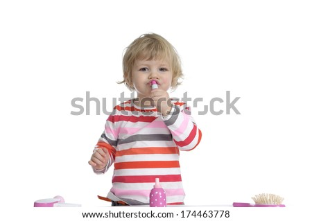 little toddler playing with make-up toys