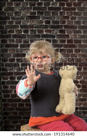 little toddler with glasses and teddy bear saying hello against a brick wall