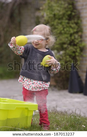 little toddler with glasses playing with sand in the garden