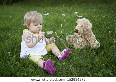 little toddler with teddy bear, seated in the garden - stock photo