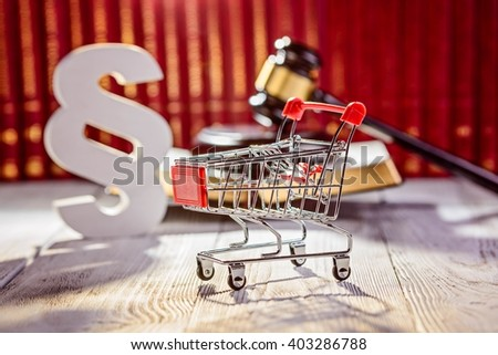 Little trolley - pushcart with the symbols of law in court library with legal codes. Commercial law concept