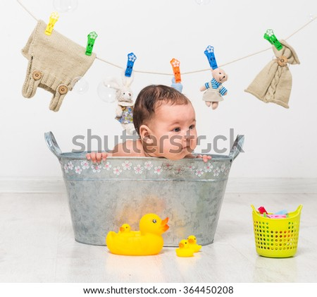 little two-month girl bathes in a  trough and dry her clothes - stock photo