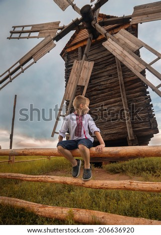 little ukrainian boy is sitting on the hedge near old wooden mill