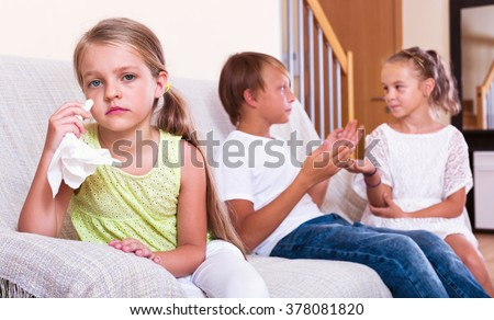 Little  upset girl is jealous sister of stepbrother indoors - stock photo