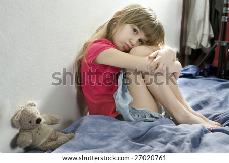 little upset girl sitting on the bed hugging her knees