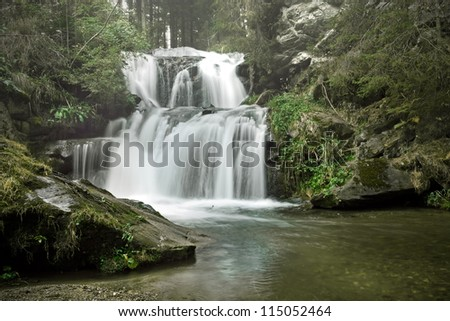 Little waterfall in the forest with fog
