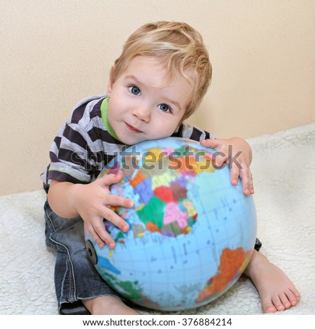 little white boy in jeans laid his head on the globe. Baby embraced the globe. We need to protect the planet for Children - stock photo