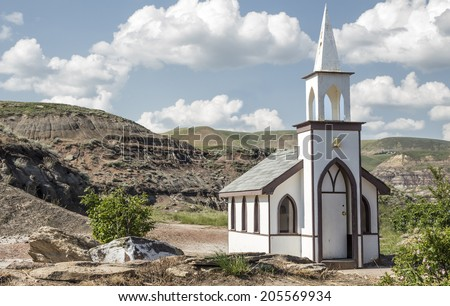 little white country church nestled in the hills with a blue sky with white clouds on a bright summer day - stock photo