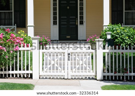 Little white gate and picket fence with roses. Frontal view, high contrast, porch and house facade in background - stock photo
