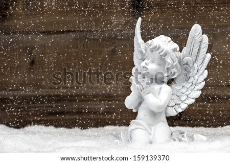 little white guardian angel in snow on wooden background. vintage style christmas decoration with falling snowflakes effect - stock photo