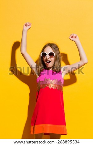 Little winner girl. Happy girl in sunglasses and mini dress shouting with arms raised. Three quarter length studio shot on yellow background. - stock photo