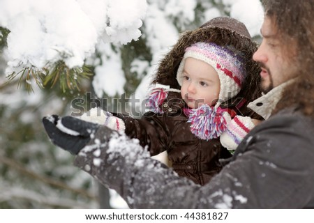 Little winter baby girl and her father touching tree branch