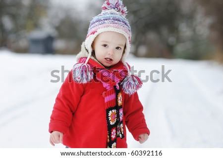 Little winter baby girl in red coat