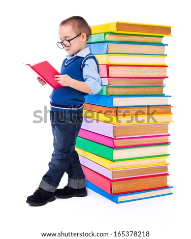 Little wise boy reading book near big stack of colorful books - stock photo