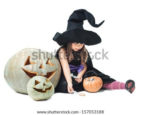 little witch sits near pumpkin and considers candies