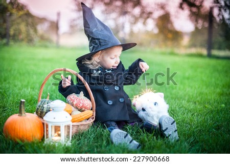 Little witch with cat - stock photo