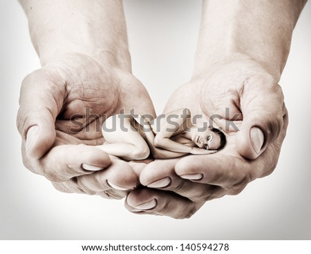 little woman is sleeping in the men's hands. Loving couple - stock photo