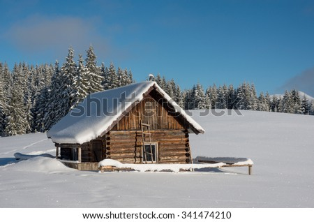 Little wood house against winter landscape. All trees and hut are covers with snow. Beautiful sunny winter day. - stock photo