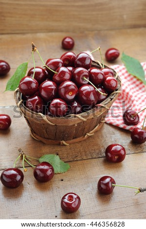 Little wooden basket of fresh ripe cherries on the wooden table
