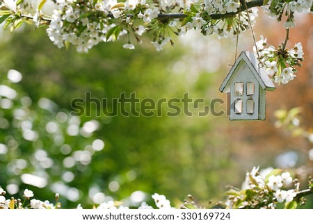 Little wooden house in Spring with blossom cherry flower sakura - stock photo