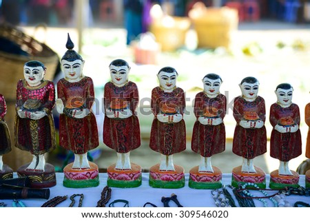 Little wooden monk statues are sold in handicraft product shop in Myanmar - stock photo