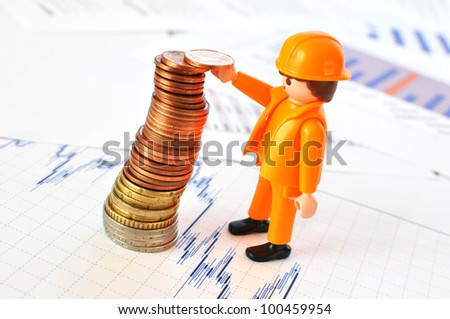 Little worker build a pyramid of coins - stock photo
