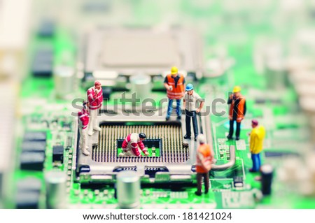 Little workers repairing motherboard. Technology concept - stock photo