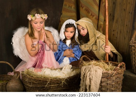 Little 7 year old angel visiting a nativity scene reenacted with a doll - stock photo