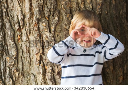 Little 4 year old blond caucasian boy in front of an old and massive tree pretending to take a picture with his hands - stock photo