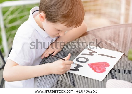 "Little 7 year old boy paints greeting card for Mom on Mother's Day with the inscription ""I love you mom"". Outdoors. Mother's Day"