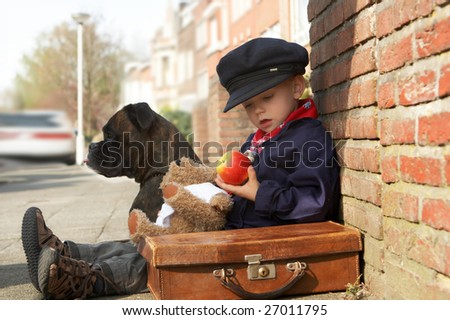 Little 4 year old boy with a suitcase and his dog - on the road together - stock photo