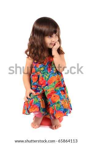 Little 3 year old girl sitting on a small stool holding her hand to her face with a wondering look on a white background - stock photo