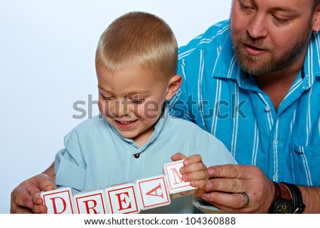 little 3 year old toddler boy and his father playing with wooden abc alphabet blocks on studio background. - stock photo