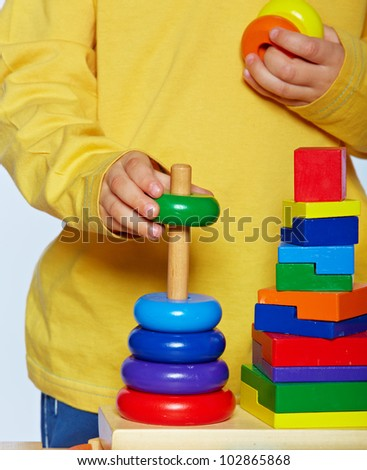 little 3 year old toddler boy playing with bright wooden pyramid over light studio background - stock photo
