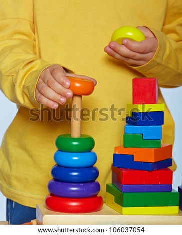 little 3 year old toddler boy playing with bright wooden pyramid over light studio background. - stock photo