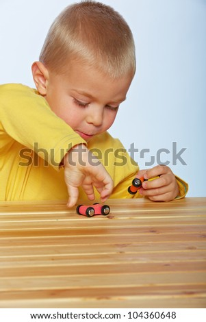 little 3 year old toddler boy playing with wooden cars on studio background