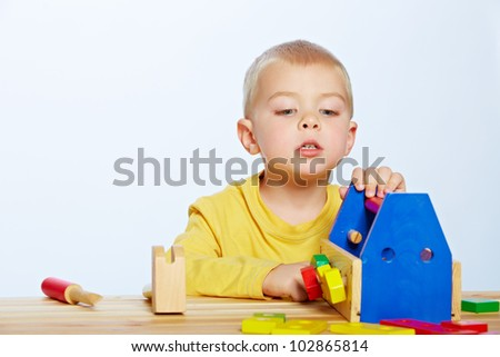 little 3 year old toddler boy with a wooden toolbox and tools over studio background - stock photo