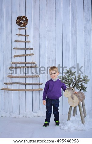 Little 4 years boy hugs stylish wooden Christmas deer decoration near frosted branch hanging Christmas tree beautiful alternative to traditional version Scandinavian New Year decor