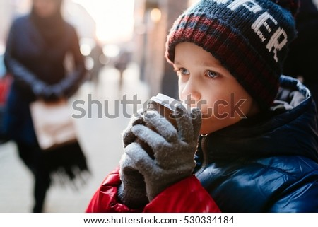 Little 7 years old boy drinking hot cocoa from paper mug outdoors