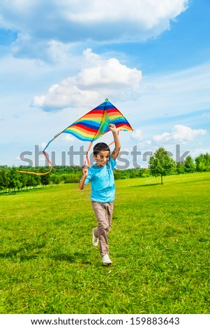 Little 6 years old boy in blue shirt running with kite in the field on summer day in the park