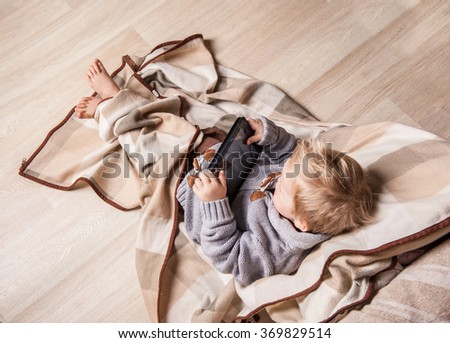 little  2 years old toddler boy using touch pad at home