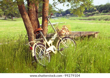 Little yellow bicycle standing on green meadow - stock photo