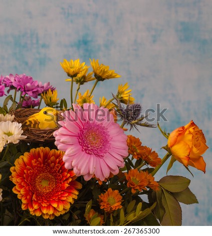 Little yellow bird in a bouquet of spring flowers, selective focus - stock photo