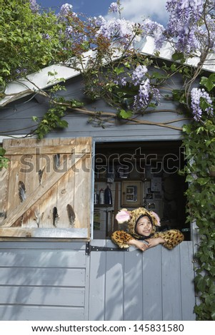 Little young boy in jaguar costume in shed smiling - stock photo
