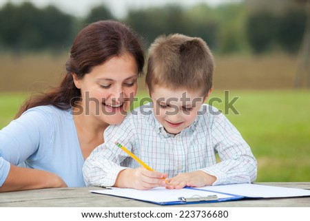 Little young boy in white shirt and his happy mother having fun writing or drawing with a pencil on a sheet of paper on wood table in the park  - stock photo