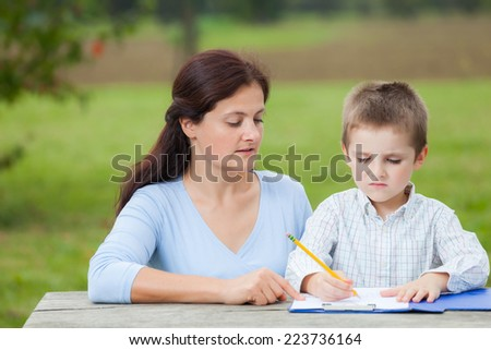 Little young boy in white shirt and his mother write or draw with a pencil on a sheet of paper on wood table in the park  - stock photo