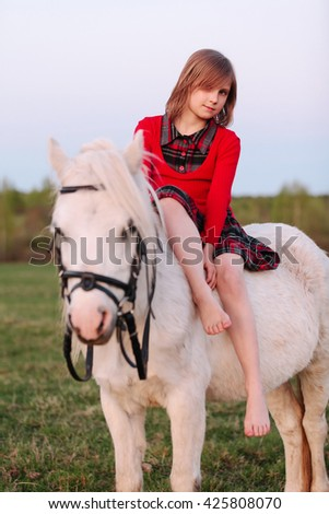 Little young girl sitting astride a white horse and smiling Outdoors - stock photo
