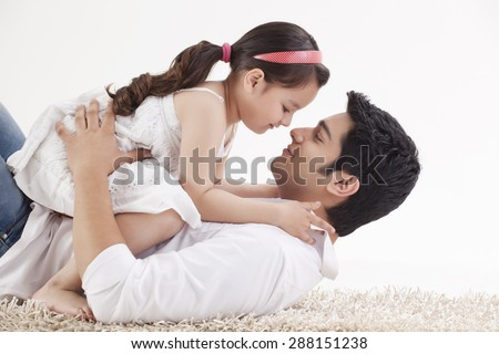 Little young girl sitting on father's stomach - stock photo