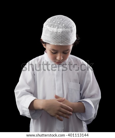 Little Young Muslim Boy Praying Over Black Background - stock photo